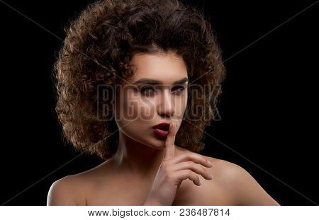 Charismatic curly model posing on black background. Girl having intresting hairstyle with many curles and accurate day make up with saturated bright lipstick. Beatiful opened shoulders. stock photo