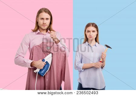 Ruining stereotypes. Handsome young man ironing a shirt and his girlfriend posing with a hammer while posing against pink and blue backgrounds stock photo