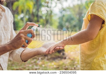dad and son use mosquito spray.Spraying insect repellent on skin outdoor. stock photo