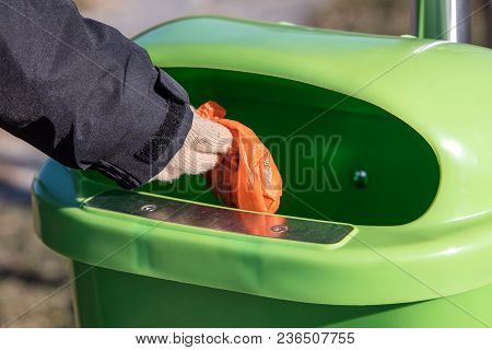 Woman putting a excrement bag from a dog into a waste bin containter, defecation of dog dirt stock photo
