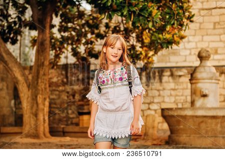 Adorable little girl tourist with backpack on the streets of Provence at sunset, travel with kids stock photo
