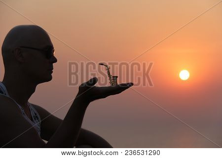 Male saxophonist at sunset. Alto saxophone at sunset. Silhouette of a mini saxophone. stock photo