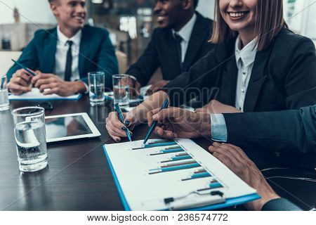 Colleagues in business suits study charts depicted in negotiation room. Business Meeting. Encounter in Boardroom. stock photo