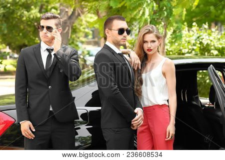 Young businesswoman with bodyguards near car outdoors stock photo
