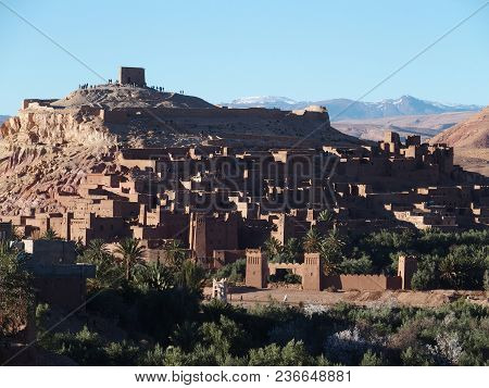 Kasbah Ait Ben Haddou or Benhaddou fortified city with green exotic palm trees at oasis on african Atlas Mountains range landscapes of Morocco, clear blue sky in 2017 warm sunny winter day, February stock photo