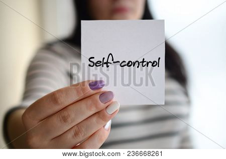 Young sad girl shows a white sticker. Caucasian brunette holding a sheet of paper with message. Self-control stock photo