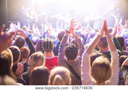 The audience applauds the artists. They shines the spotlight. stock photo