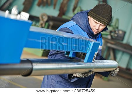 Sheet metal folding. industrial worker with piple on rolling bending machine stock photo