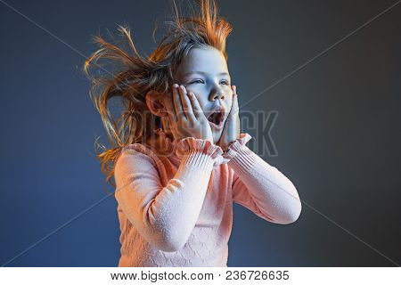 The anger and surprised teen girl. Hate, rage. Crying emotional angry teenager in colorful bright lights at studio background. Emotional face. Sport fan human emotions, facial expression concept. stock photo