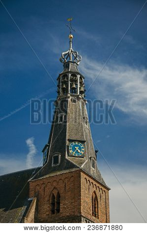 Close-up of pointed steeple roof in a church made of bricks, golden clock and sunny blue sky at Weesp. Quiet and pleasant village full of canals and green near Amsterdam. Northern Netherlands. stock photo