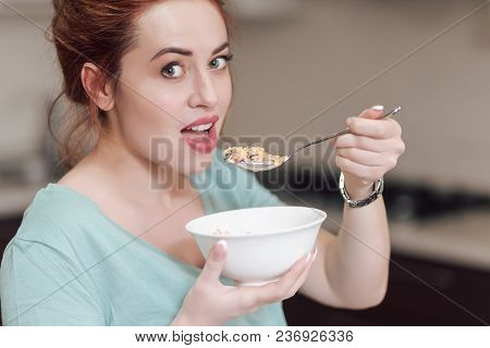 Beautiful pregnant woman eating with lust cereals on breakfast, enjoying meal. Yummy food for pregnant ladies stock photo