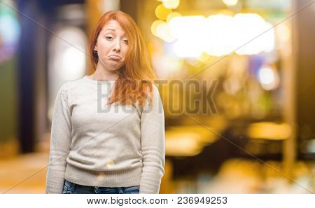 Beautiful young redhead woman having skeptical and dissatisfied look expressing Distrust, skepticism and doubt at night stock photo
