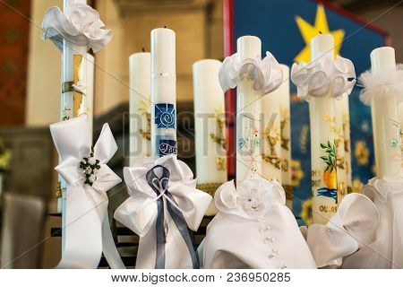 First holy communion or confirmation - burning candles rowed up in church before ceremony beautiful decoration stock photo