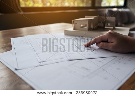 An architect working on an architecture model with shop drawing paper on table stock photo