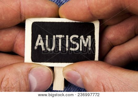 Writing note showing  Autism. Business photo showcasing Autism Awareness conducted by social committee around the globe written Wood Piece holding by man the Blue Jeans background. stock photo