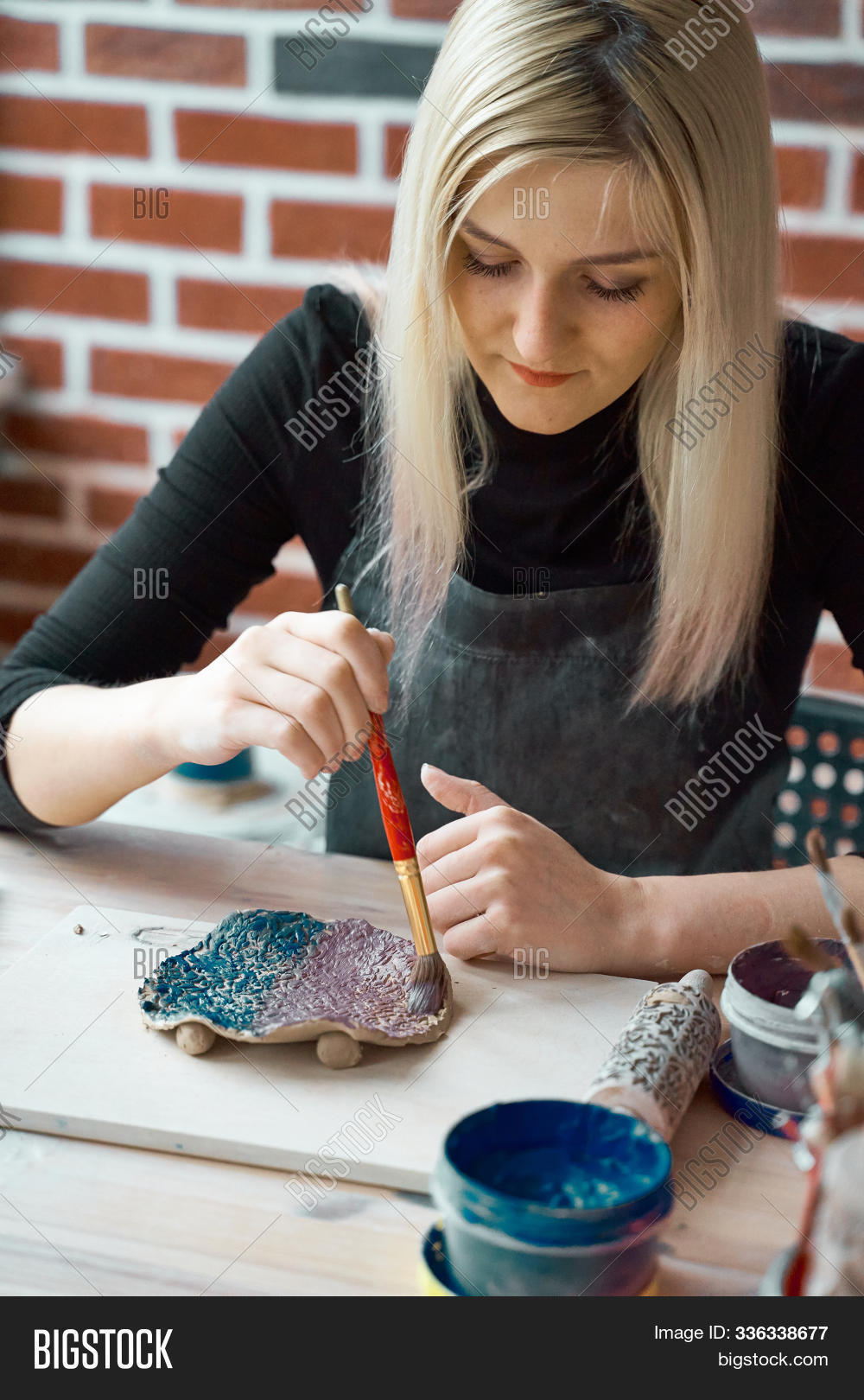 Woman making pattern on ceramic plate with paint brush. Creative hobby concept. Earn extra money, side hustle, turning hobbies into cash, passion into job, vertical