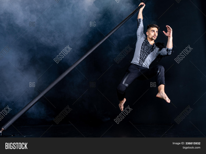 acrobat,acrobatics,aerial,artist,artistic,athlete,background,caucasian,circus,concept,costume,dance,dancer,demon,devil,figure,fly,fog,guy,gymnast,gymnastics,healthy,lifestyle,male,man,out,pole,power,raven,show,smoke,sport,sportsman,strong,studio,torso,trick