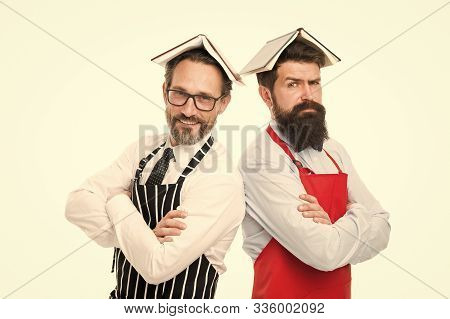 Responsibilities of household. Men bearded apron reading book about culinary. Men in charge household. Some problems. Household duties. Book as roof on head. Household is boring. Who rules in house. stock photo