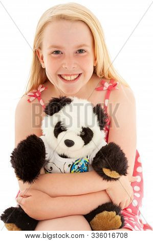 Close up of smiling beautiful young blonde girl cuddling her teddy bear and making eye contact. Isolated on white studio background stock photo