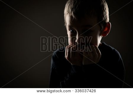 Grief-stricken little boy - feeling intense sorrow, remorse, sadnesss - studio portrait - vivid emotions series stock photo