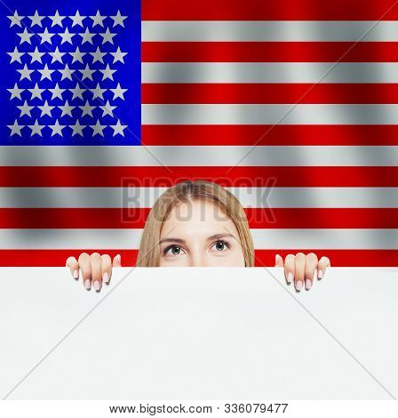 Portrait of happy american girl with white paper against the USA flag background. Travel and learn english language concept stock photo