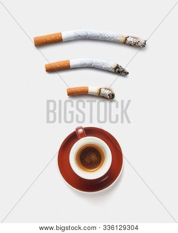 Three roach cigaretts around a cup of coffee as a wireless simbol on a light grey background with copy space. Concept of addiction from smoking and gadgets. stock photo