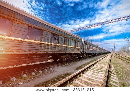 Abandoned railway station . Rusty weathered peeled paint of an old wagon. Blue railway carriage. Wooden sleepers or cross ties. stock photo