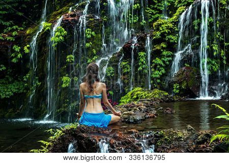 Caucasian woman standing on the rock, practicing yoga. Young woman raising arms with namaste mudra near waterfall. Banyu Wana Amertha waterfall Wanagiri, Bali, Indonesia. View from back. stock photo