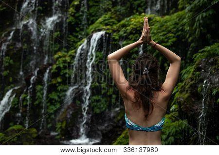 Close up of yoga woman raising arms with namaste mudra in front of waterfall. View from back. Yoga retreat. Meditation practice. Banyu Wana Amertha waterfall Wanagiri, Bali, Indonesia. stock photo