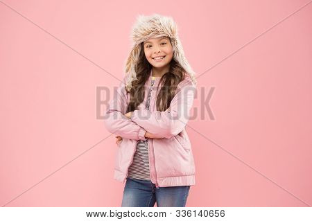 Christmas vacation. warm clothes for cold season. fur earflap hat accessory. small girl winter hat. autumn style. Childhood activity. kid fashion. girl look like hipster. happy child pink background. stock photo