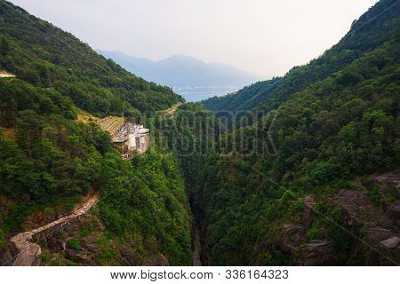 View from the Contra Dam over a hydroelectric power plant on the Verzasca River in Ticino, Switzerland. This dam is also known as the Verzasca Dam and the Locarno Dam. stock photo