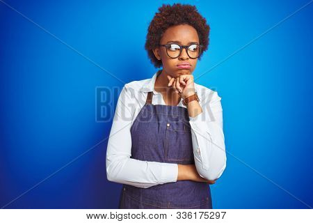 Young african american woman shop owner wearing business apron over blue background thinking looking tired and bored with depression problems with crossed arms. stock photo
