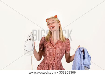 Girl holding iron in hand. Beautiful woman holds steam iron. Housework and household concept - housewife ironing clothes. Retro woman ironing clothing. Housekeeper woman in uniform with iron in hand. stock photo