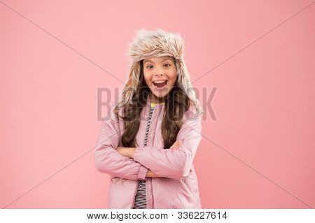 Posing for photo. autumn style. Childhood activity. kid fashion. girl look like hipster. fur earflap hat accessory. small girl winter hat. warm clothes for cold season. happy child pink background. stock photo