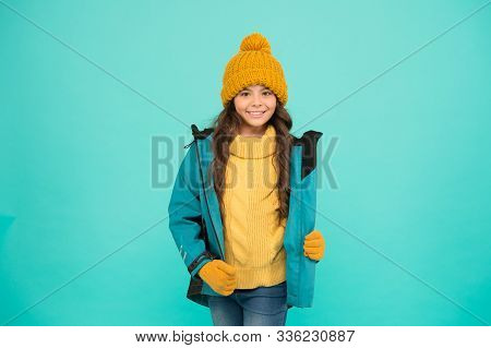 Winter sports. knitted clothes fashion. cold season weather. outdoor activity for kids. small girl sweater. hat and gloves accessory. warm clothes sales. happy girl down jacket. Winter holidays. stock photo