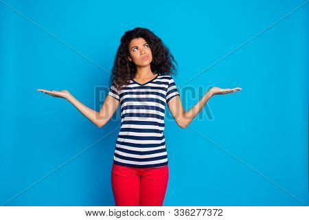 Hmm what choose. Portrait of thoughtful dreamy  girl hold hand compare ads cant decide right solution think feel unaware wear striped t-shirt red pants trousers isolated blue color background stock photo