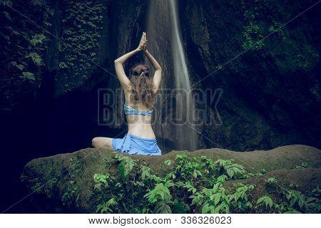 Caucasian woman sitting on the rock, practicing yoga. Young woman raising arms with namaste mudra near waterfall. Leke Leke waterfall, Bali, Indonesia. View from back. Yoga retreat. Copy space. stock photo