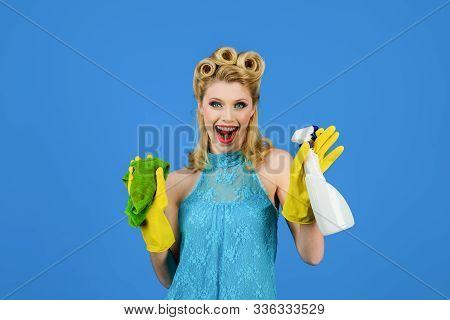 Cleaning service. Cleaning woman. Cleanup. Cleaning tools. Beautiful woman holds duster and spray. Happy retro housewife. Housewife ready for housework. Girl cleaning with rag and bottle spray. stock photo