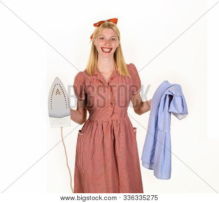 Girl holding iron in hand. Housekeeper woman in uniform with iron in hand. Beautiful woman holds steam iron. Housework and household concept - housewife ironing clothes. Retro woman ironing clothing. stock photo