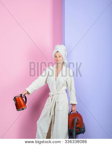 Smiling sexy woman with vacuum cleaner and kettle. Housewife with vacuum cleaner and electric kettle in hands. Woman in bathrobe and towel on head. Happy woman with vacuum cleaner and kettle at home. stock photo