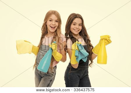 Dirt is not welcome in our home. Adorable little girls wearing household rubber gloves. Small children holding household spray bottles. Enjoying household activities. Providing household help. stock photo