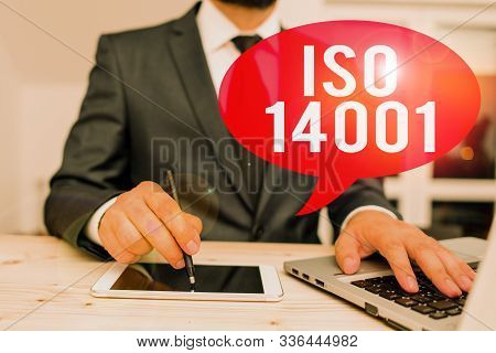 Word writing text Iso 14001. Business concept for a family of standards related to environmental analysisagement Male human wear formal clothes present presentation use hi tech smartphone. stock photo