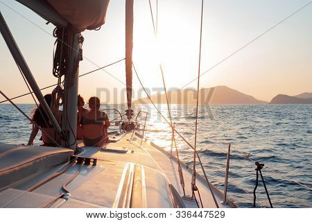 Girls sit on the deck of the yacht and enjoy the sunset. Boat trip on a yacht under sail, a fragment of the deck and the mountains on the horizon, view from the deck. Sailing and yachting, lifestyle stock photo