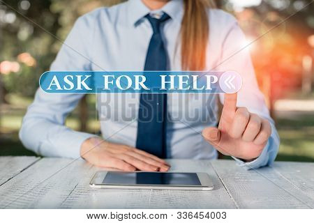 Handwriting text Ask For Help. Concept meaning Request to support assistance needed Professional advice Female business person sitting by table and holding mobile phone. stock photo