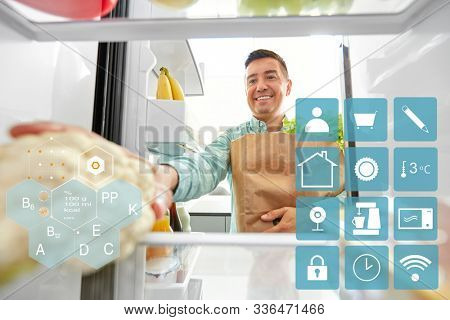 eating, diet and storage concept - smiling middle-aged man with new purchased food in paper bag putting cauliflower to fridge at kitchen over blue and white smart home app icons stock photo