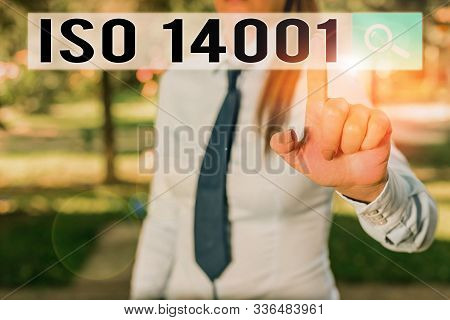Writing note showing Iso 14001. Business photo showcasing a family of standards related to environmental analysisagement Handsome business girl pointing with finger into empty space. stock photo