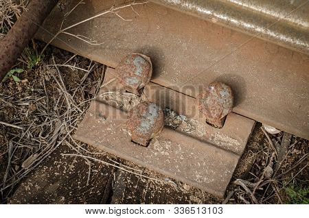 Close-up of a rusty rail lining. Old metal lining for a crutch joint of a rail on wooden sleepers. View from above. Elements of an abandoned railway. stock photo