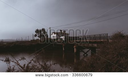 A mysterious morning foggy scenery with an old rusty bridge and a small river in the middle, dry bushes in the foreground, a small abandoned house with empty window holes in a background, Alcochete stock photo