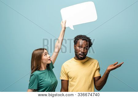 girl holding speech bubble above confused african american man showing shrug gesture on blue background stock photo