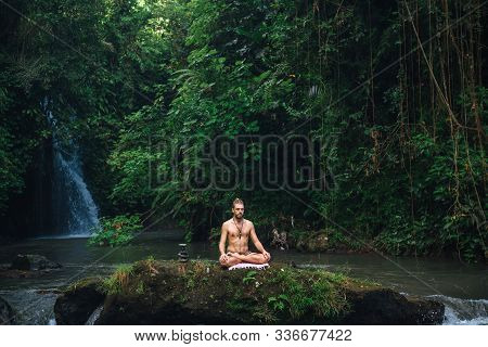 Yoga practice and meditation in nature. Man practicing near river. stock photo